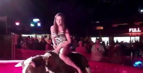 Девушка забралась на механического быка в очень коротком платье